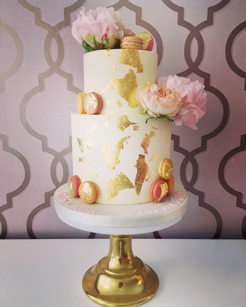 Hochzeitstorte mit Blattgold, Blumen und Macarons
